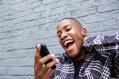Young african man reading a funny text message on his phone Stock Photos