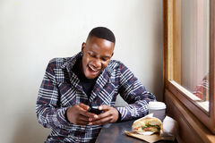 Young african man reading a funny text message Stock Photos