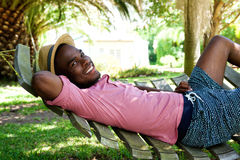 Young african man relaxing outdoors on a hammock stock photo