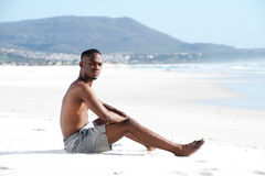 Young african man sitting alone at beach. Side portrait of young african man sitting alone at beach Stock Photo