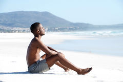 Young african man sitting alone on the beach. Side view portrait of young african man sitting alone on the beach Stock Photos