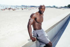 Young african man sitting on a beach embankment. Portrait of muscular young african man sitting on a beach embankment looking at camera. Shirtless young man Stock Photos