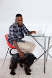 Young african man sitting at home with his pet dog and laptop Royalty Free Stock Photo