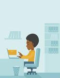 Young african man sitting infront of a computer Royalty Free Stock Photography