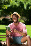 Young african man sitting outdoors with a digital tablet Royalty Free Stock Photo