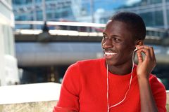 Young african man sitting outdoors and listening music. Portrait of young african man sitting outdoors and listening music on earphones Stock Photo