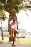 Young african man skateboarding outdoors in park Royalty Free Stock Image