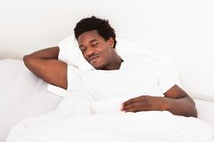 Young african man sleeping in bed Royalty Free Stock Photography