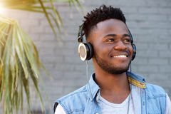 Young african man smiling with headphones by palm tree Royalty Free Stock Images