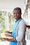 Young african man smiling in library. African american male college student leaning on shelf in library and looking at camera. Vertical shape, waist up, front Royalty Free Stock Photography