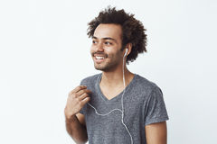 Young african man smiling putting out one wired headphone over white wall listening to birds. Stock Images