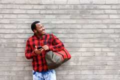 Young african man standing against wall with bag and cellphone. Portrait of young african man standing against wall with bag and cellphone Royalty Free Stock Photos