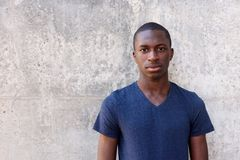 Young african man standing agaisnt gray wall. Close up portrait of young african man standing agaisnt gray wall Stock Images
