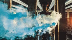 Young African man stands under bridge and holds colored blue smoke bomb. Young African man in jeans stands in water under bridge and holds colored blue smoke royalty free stock photography
