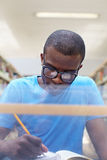 Young african man studying in library. African american male college student sitting at desk in library and reading book. Reflections of paperwork on eyeglasses Royalty Free Stock Images