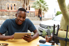 Young african man using digital tablet at a cafe. Portrait of young african man sitting at outdoor cafe and using digital tablet Stock Photos