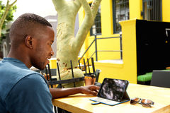 Young african man using digital tablet at a cafe Royalty Free Stock Image
