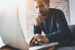 Young African man using laptop while sitting at his modern coworking place.Concept of business people full concentration. Blurred background, flares Stock Image