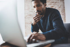 Young African man using laptop while sitting at his modern coworking place.Concept of business people full concentration. Brick wall on blurred background royalty free stock photos