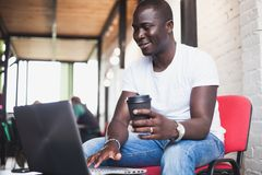 Full concentration. Close-up part of young African man using laptop while sitting at his working place Stock Photo