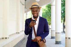 Young african man walking with cellphone and bag Royalty Free Stock Photos