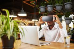 African man watching video and playing game in virtual glasses. Royalty Free Stock Photos