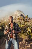 Young African man out for a hike in the wilderness. Young African man wearing a backpack standing on a trail while hiking alone in the hills on a sunny day royalty free stock image
