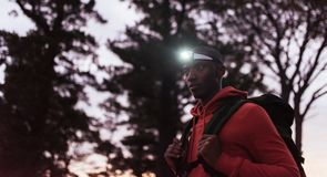 Young African man wearing a headlamp jogging at dusk. Focused young African man wearing a headlamp standing alone in the forest while out for a cross country run Stock Photo