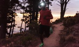 Young African man wearing a headlamp jogging at dusk. Young African man wearing a headlamp running alone down a trail in the forest while out for a cross country stock images