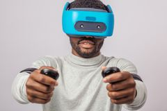 Young african man wearing virtual reality goggles isolated on white background stock photo