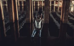 Young African man stands in water under bridge on background of. Young African man in white tank top and jeans stands in water under bridge on background of royalty free stock photography