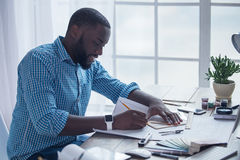 Young african man working in the office business. Young african male working in the office business architect drawing project Stock Photos