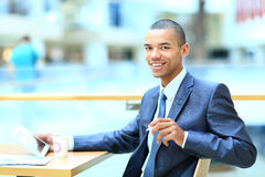 Young african manager sitting at desk in bright office Stock Photo