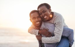 Smiling African couple enjoying a carefree day at the beach. Young African men carrying his smiling girlfriend on his back while enjoying a late afternoon royalty free stock photos