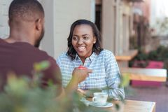 Smiling young African woman getting a gift from her boyfriend stock photography
