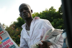 Young african men, offers newspapers to drivers in traffic jam. Stock Images