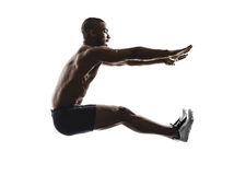 Young african muscular build long jumping   man silhouette. One young african muscular build man long jumping silhouette  isolated on white background Stock Photos