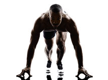 Young african muscular build man on starting blocks silhouette. One young african muscular build man on starting blocks silhouette  isolated on white background Royalty Free Stock Images