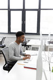 Young african office worker sitting at a desk Royalty Free Stock Photos