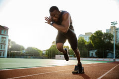 Young african runner running on racetrack. At the athletics stadium Royalty Free Stock Images