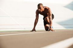 Young african runner starting and preparing to run. On the competition running performance track Royalty Free Stock Image
