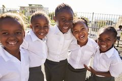 Young African schoolgirls in playground smiling to camera Royalty Free Stock Images