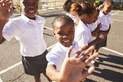 Young African schoolgirls in a playground waving to camera Royalty Free Stock Image