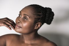 Young African woman with a beautiful complexion touching her chin. Young plus size African woman with a beautiful complexion standing alone against a white royalty free stock image