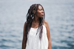 Young African woman with braids near the sea, eyes closed royalty free stock images