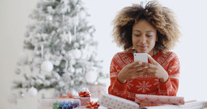Young African woman checking for Xmas messages. On her mobile phone as she sits wrapping gifts in front of the Christmas tree Stock Photo