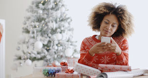 Young African woman checking for Xmas messages Stock Images