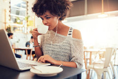 Young african woman drinking coffee and using laptop at a cafe Stock Images