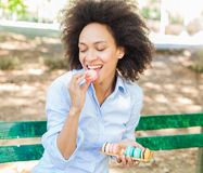 Young African Woman Eating Macarons Cookie In The Park royalty free stock photo