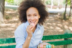 Young African Woman Eating Macarons Cookie In The Park royalty free stock images